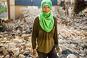 "11 DECEMBER 2012 - BANGKOK, THAILAND: A demolition worker at ""Washington Square"" a notorious entertainment district off Sukhumvit Soi 22 in Bangkok. Demolition workers on many projects in Thailand live on their job site tearing down the building and recycling what can recycled as they do so until the site is no longer inhabitable. They sleep on the floors in the buildings or sometimes in tents, cooking on gas or charcoal stoves working from morning till dark. Sometimes families live and work together, other times just men. Washington Square was one of Bangkok's oldest red light districts. It was closed early 2012 and is being torn down to make way for redevelopment.    PHOTO BY JACK KURTZ"