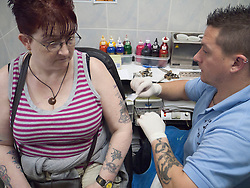 Person with disability having a tattoo in tattoo parlour - applying transfer of design