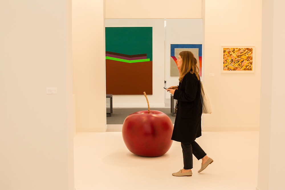 "New York, NY - May 3, 2019. A woman passes Claude Lalanne's painted bronze ""Pomme de Jardin"" in the Kasmin Gallery at the Frieze Art Fair on New York City's Randalls Island."