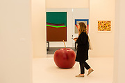 """New York, NY - May 3, 2019. A woman passes Claude Lalanne's painted bronze """"Pomme de Jardin"""" in the Kasmin Gallery at the Frieze Art Fair on New York City's Randalls Island."""