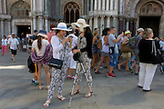 Girl tourists in similar clothing outside Basillica di San Marco in Piazza San Marco, Venice, Italy