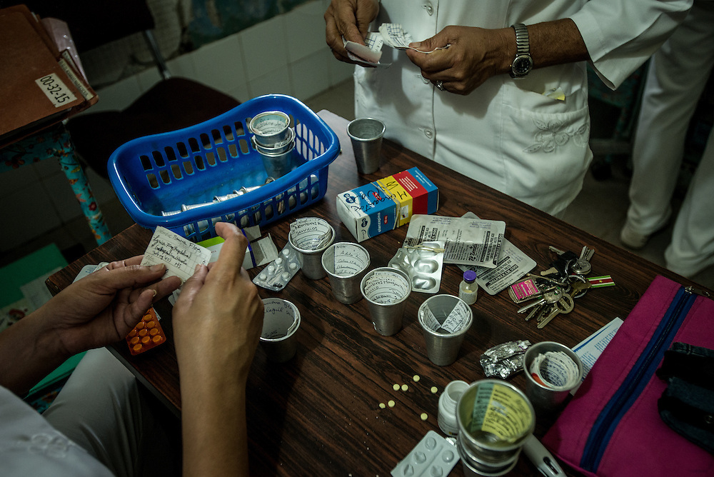 BARQUISIMETO, VENEZUELA - AUGUST 24, 2016: Nurses debate with each other about which patients are the most unstable, to decide which patients will receive the limited number of pills on hand, and which will go without. The hospital has not employed a psychiatrist in over two years, so even though they are not doctors, the nursing staff find themselves responsible for doing a psychiatrist's work - they make decisions about how to medicate patients - modifying doses and swapping one patient's pills to give to another, who might be more unstable and need them more. They reference medical files from two years ago when a licensed psychiatrist was on staff - all written by hand and kept in paper folders. They use a mix of the old treatment plans from two years ago, plus their own observations of the patient, and modify treatments and care based on years of learning from trial and error.   The economic crisis that has left Venezuela with little hard currency has also severely affected its public health system, crippling hospitals like El Pampero Psychiatric Hospital by leaving it without the resources it needs to take care of patients living there. Drugs used to combat bipolar disorder, epilepsy, schizoaffective disorder and chronic anxiety are now in short supply, as are numerous sedatives and tranquilizers needed to care for patients. When a patient loses control, often the only thing they can do is lock them in an isolation cell to prevent them from hurting themselves, other patients and members of the staff.  PHOTO: Meridith Kohut for The New York Times