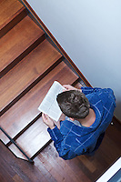 Man reading newspaper on stairs
