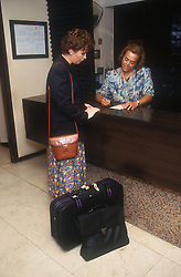 Woman checking into hotel at reception,