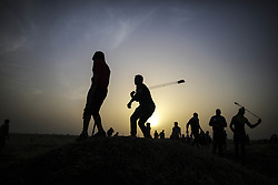 April 6, 2018 - Gaza, Palestinian Territory - Palestinian protesters use slingshots to hurl stones at Israeli troops during clashes on the Gaza-Israel border, east of Gaza City. At least 18 Palestinians have been killed and over 1,200 others injured since last Friday, when a massive Palestinian protest was launched to mark the Palestinian Land Day along the border between Gaza and Israel. (Credit Image: © Wissam Nassar/Xinhua via ZUMA Wire)