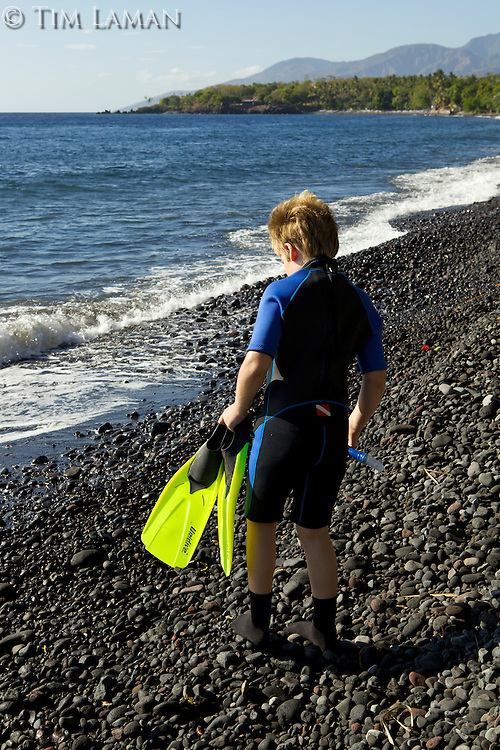 A 9 year-old boy walks across the rocky beach at Tulamben with snorkeling gear.