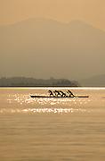 Four men rowing in the Venetian style known as 'Voga alla Veneta', on Lake Garda, Italy