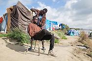 Calais, Pas-de-Calais, France - 17.10.2016    <br />  <br /> A Sudanese refugee gets his hair cut by another camp residents. &rdquo;Jungle&quot; refugee camp on the outskirts of the French city of Calais. Many thousands of migrants and refugees are waiting in some cases for years in the port city in the hope of being able to cross the English Channel to Britain. French authorities announced that they will shortly evict the camp where currently up to up to 10,000 people live.<br /> <br /> Ein sudanesischer Fluechtling bekommt von einem andern Camp-Bewohner seine Haare geschnitten. &rdquo;Jungle&rdquo; Fluechtlingscamp am Rande der franzoesischen Stadt Calais. Viele tausend Migranten und Fluechtlinge harren teilweise seit Jahren in der Hafenstadt aus in der Hoffnung den Aermelkanal nach Gro&szlig;britannien ueberqueren zu koennen. Die franzoesischen Behoerden kuendigten an, dass sie das Camp, indem derzeit bis zu bis zu 10.000 Menschen leben K&uuml;rze raeumen werden. <br /> <br /> Photo: Bjoern Kietzmann
