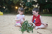2 children boy aged 5 and girl aged 3 playing in a sand box - Model release available