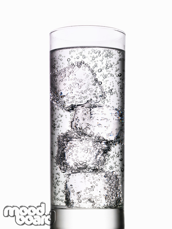 Glass of water with ice cubes on white background