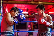 "26 SEPTEMBER 2014 - PATTAYA, CHONBURI, THAILAND: Muay Thai boxers put on a demonstration fight in a beer bar in Pataya. Pataya, a beach resort about two hours from Bangkok, has wrestled with a reputation of having a high crime rate and being a haven for sex tourism. After the coup in May, the military government cracked down on other Thai beach resorts, notably Phuket and Hua Hin, putting military officers in charge of law enforcement and cleaning up unlicensed businesses that encroached on beaches. Pattaya city officials have launched their own crackdown and clean up in order to prevent a military crackdown. City officials have vowed to remake Pattaya as a ""family friendly"" destination. City police and tourist police now patrol ""Walking Street,"" Pattaya's notorious red light district, and officials are cracking down on unlicensed businesses on the beach.     PHOTO BY JACK KURTZ"
