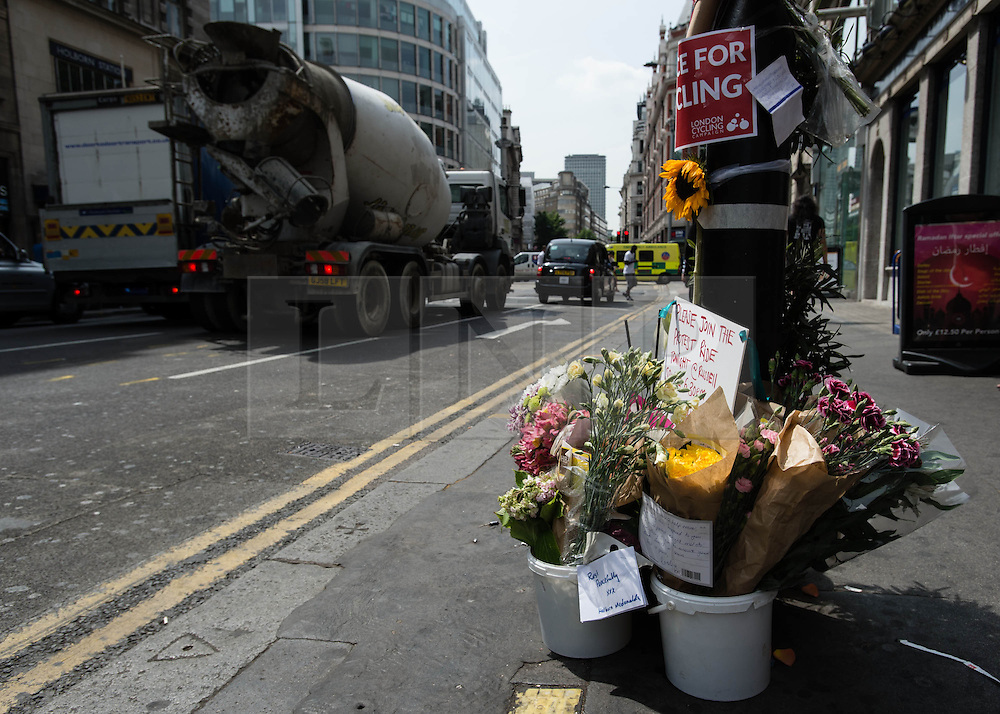 © Licensed to London News Pictures. 16/07/2013. London, UK. A cement mixer drives past a memorial to the cyclist killed yesterday by a tipper truck at the scene of the incident in central London Photo credit : Richard Isaac/LNP