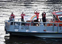 © Licensed to London News Pictures. 23/04/2020. London, UK. Members of a Fire & Rescue boat show their support for nurses, doctors and other medical staff at 8pm for the weekly Clap for Carers celebration here on the Rover Thames outside St Thomas' Hospital in central London. Lockdown continues throughout the UK in an attempt to stop the spread of the coronavirus Covid-19 virus. Photo credit: Peter Macdiarmid/LNP