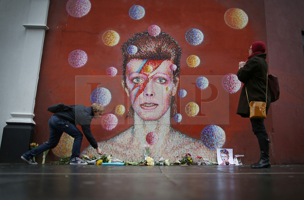 © Licensed to London News Pictures. 11/01/2016. London, UK. People visit a mural of David Bowie in Brixton. The Death of David Bowie, who was born in Brixton, has been announced today.  Photo credit: Peter Macdiarmid/LNP
