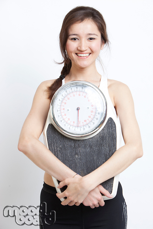 Portrait of cheerful Asian woman holding weight scale against white background