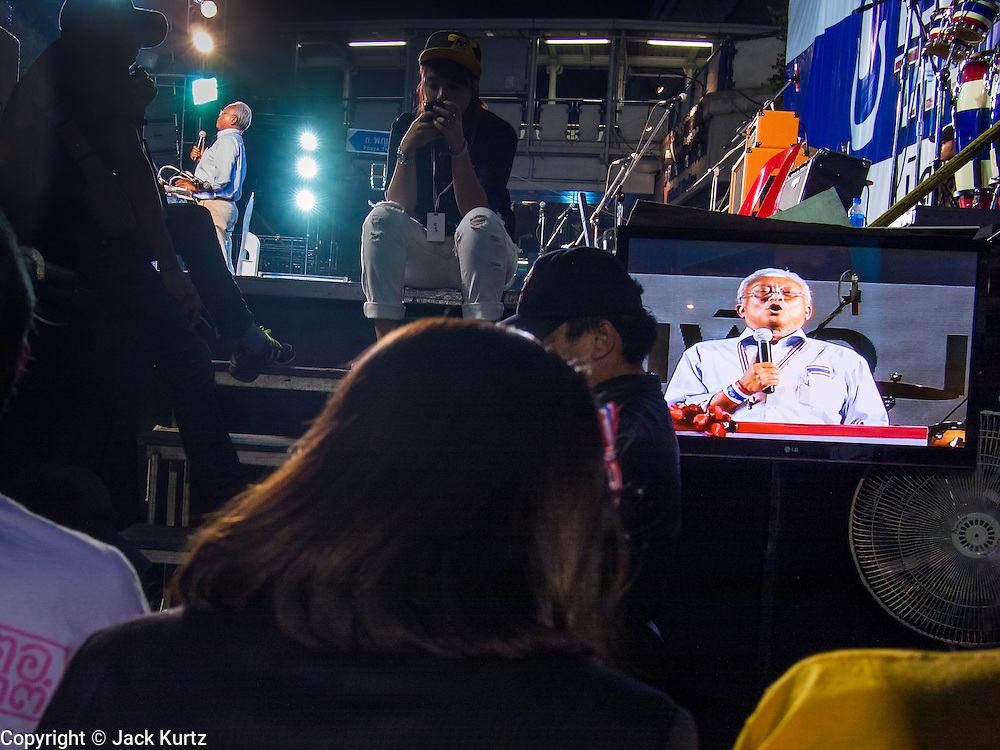 24 JANUARY 2014 - BANGKOK, THAILAND:  SUTHEP THAUGSUBAN speaks on stage at the Shutdown Bangkok Pathum Wan site while supporters backstage watch him on television. Shutdown Bangkok has been going for 12 days with no resolution in sight. Suthep, the leader of the anti-government protests and the People's Democratic Reform Committee (PDRC), the umbrella organization of the protests,  is still demanding the caretaker government of Prime Minister Yingluck Shinawatra resign, the PM says she won't resign and intends to go ahead with the election.   PHOTO BY JACK KURTZ