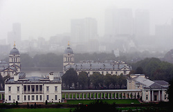 © Licensed to London News Pictures. 13/10/2013<br /> View of the National Maritime Museum at Greenwich with Canary Wharf under a blanket of fog.<br /> Wet windy and rainy weather today (13.10.2013) at Greenwich Park, London.<br /> Photo credit :Grant Falvey/LNP