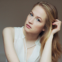 Portrait of serious young woman with blonde hair and white shirt