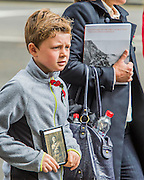 A boy carries an old picture of a relative as veterans and descendants march past. A commemoration in London to mark the Centenary of the Gallipoli Campaign 25 April 2015 at the Cenotaph on Whitehall, Westminster. Descendants of those who fought in the campaign also march past, led by military personnel, as part of the ceremony. This is an addition to the usual annual ceremony organized byvThe High Commissions of Australia and New Zealand.Guy Bell, 07771 786236, guy@gbphotos.com