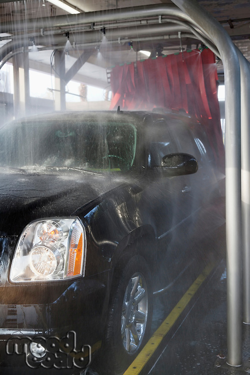 Spraying water on automobile in car wash