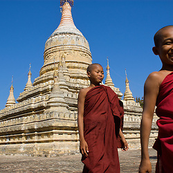 Young novice monks smile as they walk through a buddhist temple in the Bagan region of Myanmar.
