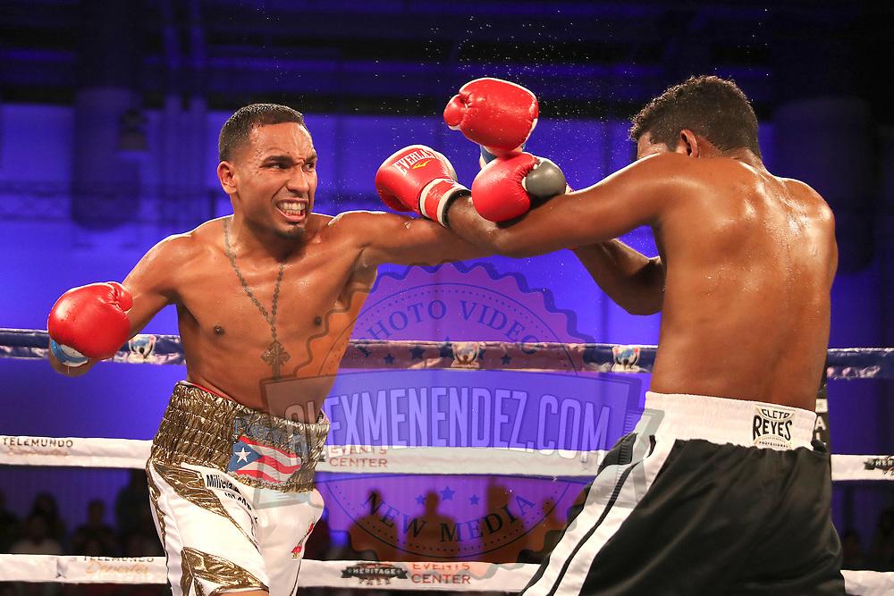 Gerald Semidy (L) punches Yasmani Pedroso during a Telemundo boxing match at Osceola Heritage Park on Friday, July 20, 2018 in Kissimmee, Florida.  (Alex Menendez via AP)