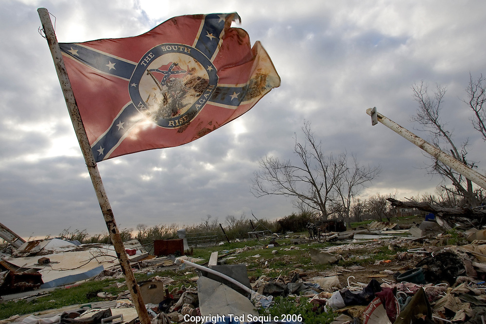 "A southern flag that reads ""The South Will Rise Again"" flies over damage in Plaquemines Parshish..Plaquemines Parish took the most heavy damage from hurricane Katrina. Located south of New Orleans, Plaquemines Parish had a large Shrimping fisherman community which was completely destroyed by Katrina. It is just starting to rebound six months after Katrina."