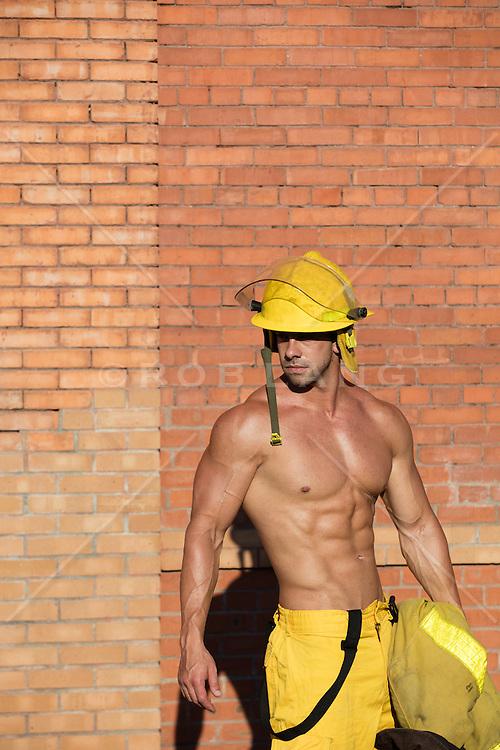 muscular fireman without a shirt outdoors