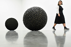 "© Licensed to London News Pictures. 11/09/2019. LONDON, UK. A staff member views (L) ""Dark Matter"", 2019, and (R) ""Inside Out"", 2019. Preview of ""Remains to be Seen"", a new exhibition by Mona Hatoum at White Cube gallery in Bermondsey.  This is the first presentation of her work since Tate Modern in 2016.  The show runs 12 September to 3 November 2019.  Photo credit: Stephen Chung/LNP"