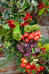 Christmas wreath detail with crab apples, holly, ivy flowers, hydrangeas and viburnum berries
