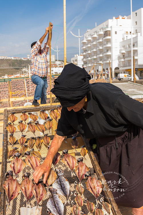 Old woman selling dried fish on the beach, Nazare, Portugal