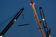 Cranes loading container ship as night