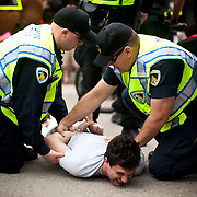 Police subdue a man after he failed to evade arrest for an open intoxicant during the Mifflin Street Block Party in Madison, WI, on May, 5, 2012. /Lukas Keapproth