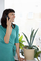 Businesswoman smiling using cell phone by plant and window
