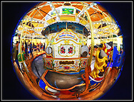 Garden City, New York, USA. March 9, 2019. Nunley's Carousel organ, seen in fisheye lens view, is surrounded by riders enjoying free rides on ornate wood horses during Unveiling Ceremony of mural by painter Michael White, held at historic Nunley's Carousel in its Pavilion on Museum Row on Long Island.