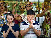 21 AUGUST 2015 - BANGKOK, THAILAND:   People pray as Thai dancers perform behind them at the Erawan Shrine. Traditionally, people who want to make merit pay the dancers to perform while they pray. The Bangkok Metropolitan Administration (BMA) held a religious ceremony Friday for the Ratchaprasong bomb victims. The ceremony started with a Brahmin blessing at Erawan Shrine, which was the target of a bombing Monday night. After the blessing people went across the street to the plaza in front of Central World mall for an interfaith religious service. Theravada Buddhists, Mahayana Buddhists, Muslims, Sikhs, Hindus, and Christians participated in the service. Life at the shrine, one of the busiest in Bangkok, is returning to normal. Friday the dancers and musicians who perform at the shrine resumed their schedules.     PHOTO BY JACK KURTZ