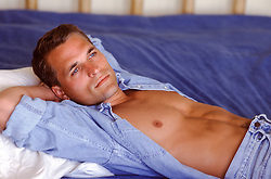 hot man in bed with an open shirt