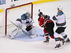 Oct 21; Newark, NJ, USA; New Jersey Devils right wing David Clarkson (23) scores a goal on San Jose Sharks goalie Antti Niemi (31) while being defended by San Jose Sharks defenseman Colin White (5) during the third period at the Prudential Center. The Sharks defeated the Devils 4-3 in an OT shootout.