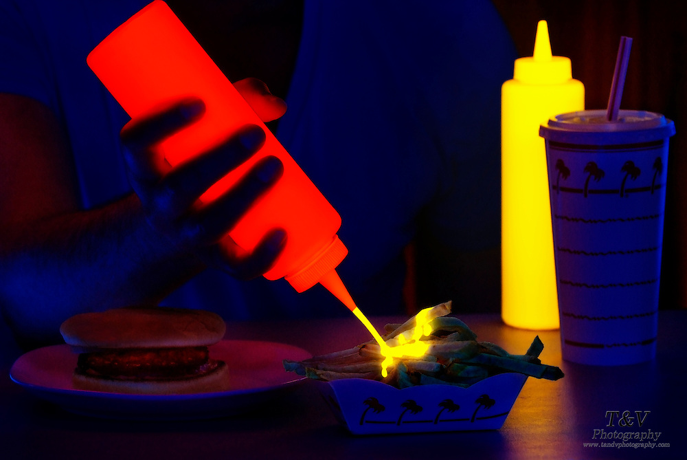A ketchup bottle spews glowing mustard on french fries.Black light