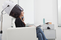 Female client sits under drying hood in hair salon