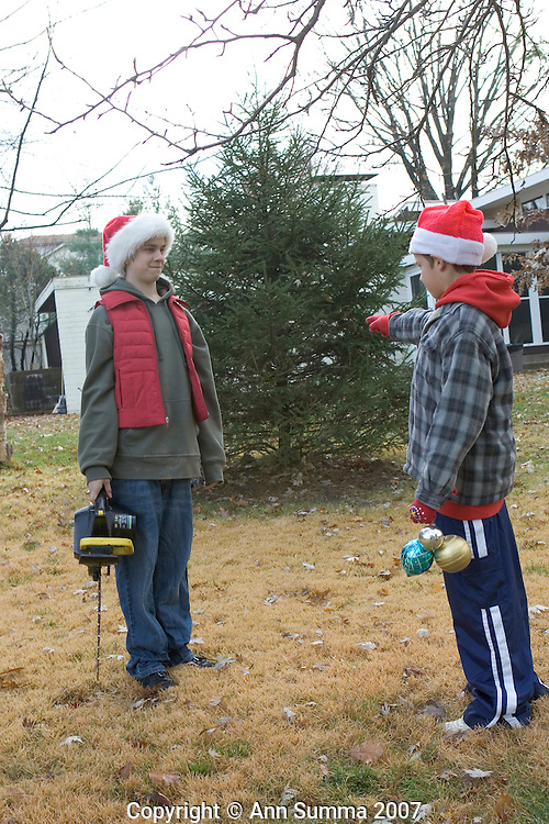 Two teen boys look for a tree to cut down for Christmas in a neighbor's yard. St. Louis, Missouri. (photo: Ann Summa).