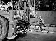 A cyclist catches a ride with a farm vehicle outside of Havana.