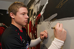 SWANSEA, WALES - Monday, March 1, 2010: Wales' Simon Church autographs a painting before training at the Liberty Stadium ahead of the international friendly match against Sweden. (Photo by David Rawcliffe/Propaganda)
