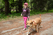 Four year old Dixie Conrow walking her dog Reba by the Bull River Guard Station, one of the original ranger statioins in the Kootenai National Forest now used as a rental cabin.