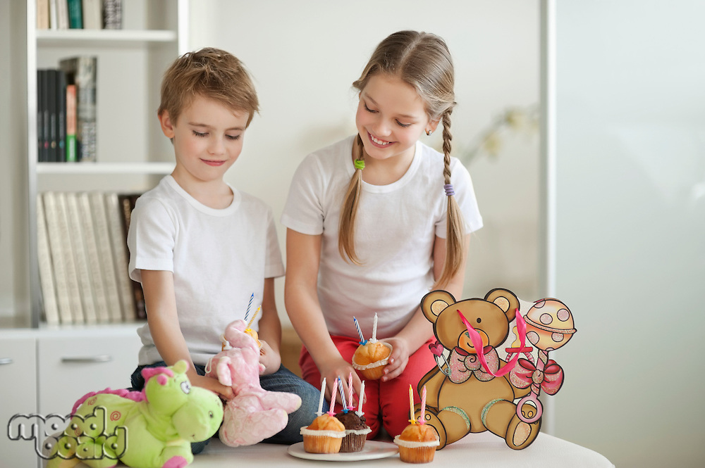 Siblings and soft toys celebrating birthday with cup cakes