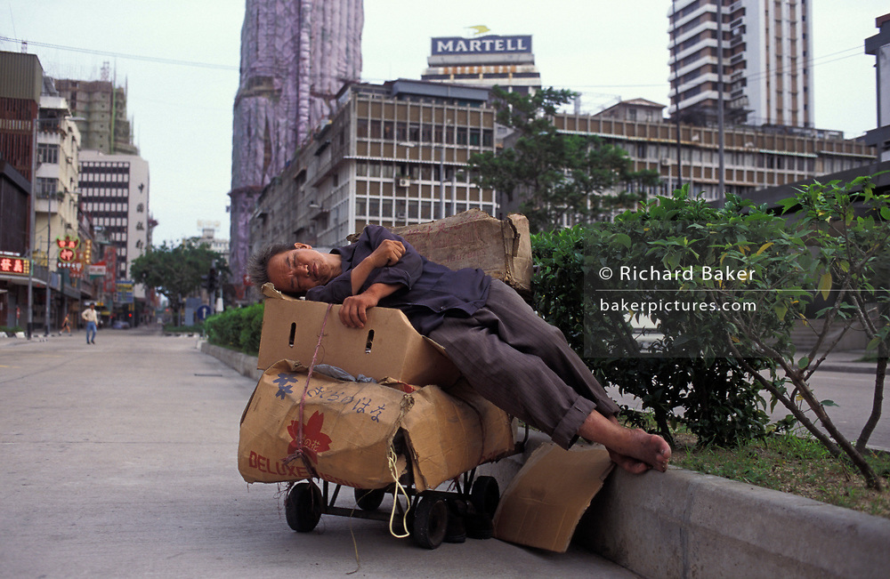 A market trader takes a mid-day sleep in the middle of the road, on 10th August 1994, in Macau, China. Macau is now administered by China as a Special Economic Region (SER), home to a population of mainland 95% Chinese, primarily Cantonese, Fujianese as well as some Hakka, Shanghainese and overseas Chinese immigrants from Southeast Asia and elsewhere. The remainder are of Portuguese or mixed Chinese-Portuguese ancestry, the so-called Macanese, as well as several thousand Filipino and Thai nationals. The official languages are Portuguese and Chinese.
