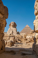 Looking down a ruined alleyway at the Sphinx and a pyramid at Giza, Egypt.