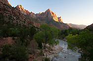 The Virgin River flows along the Pa'rus Trail as evening light illuminates the face of the mountains. Zion National Park, UT