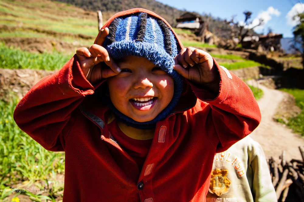 A Nepali chld smiles and laughs as he plays near the village of Chhomrong, Nepal.