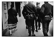 Wary Maghrebi woman and a heavy police presence in Belleville, Paris, France.